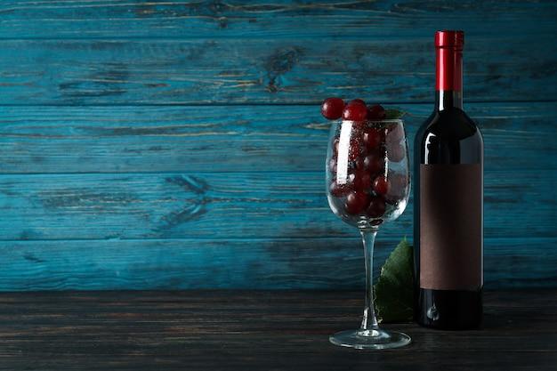 Garrafa de vinho, copo de uva e folha na mesa de madeira
