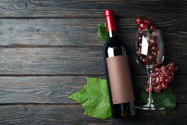 Garrafa de vinho, copo de uva e folhas na mesa de madeira