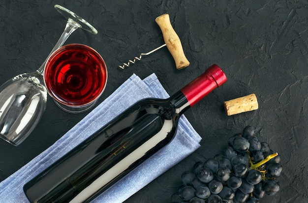 Garrafa de vinho, copo de vinho e cacho de uvas azuis na mesa escura. vista do topo.