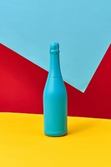 Garrafa de vinho de férias pintado de azul criativo simulado sobre um fundo amarelo vermelho azul tricolor com espaço de cópia. conceito de minimalismo.