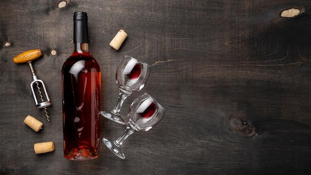 Garrafa de vinho de vista superior com copos e saca-rolhas ao lado