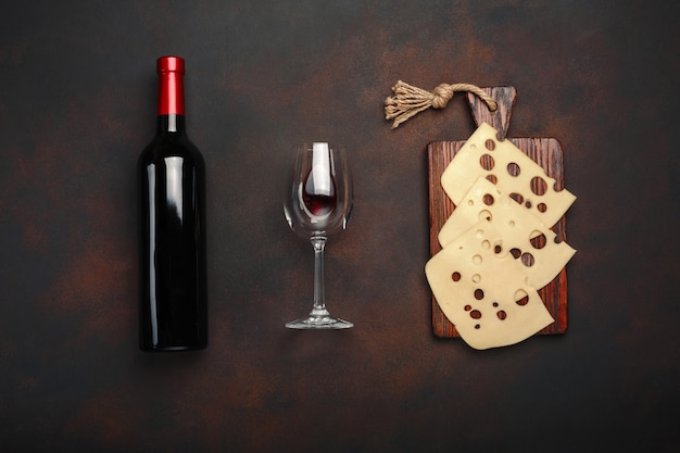 Garrafa de vinho, dois copos e queijo maasdam fatiado em uma placa de corte no fundo enferrujado