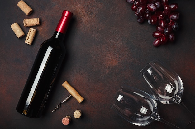 Garrafa de vinho, dois copos, saca-rolhas e rolhas, na vista superior de fundo enferrujado