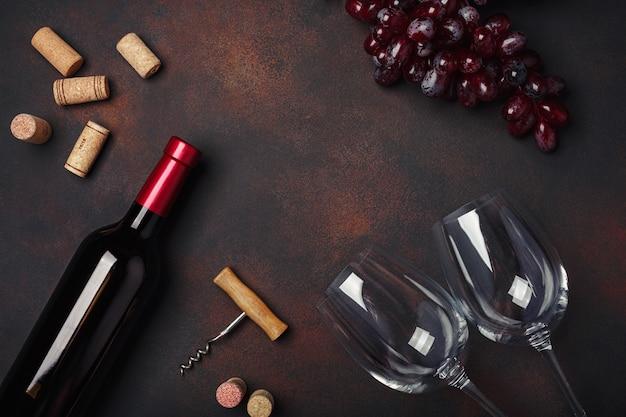 Garrafa de vinho, dois copos, saca-rolhas e rolhas, no fundo enferrujado com copyspace, vista superior