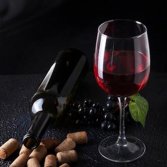 Garrafa de vinho e copo de vinho tinto em superfície de textura escura