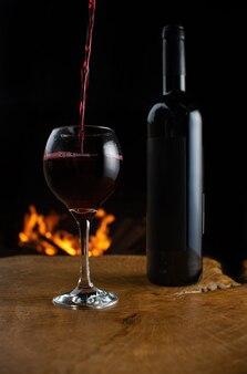 Garrafa de vinho e copo sendo enchidos com vinho em uma superfície de madeira rústica com fogo atrás