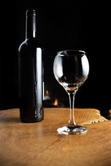 Garrafa de vinho e copo vazio na superfície de madeira rústica com fogo atrás