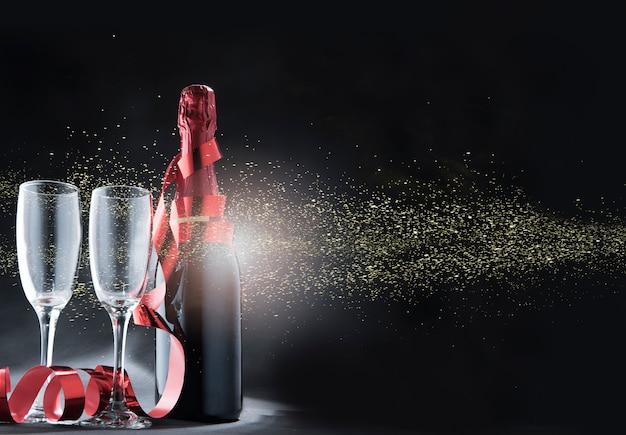 Garrafa de vinho e copos com fita vermelha e brilhos dourados