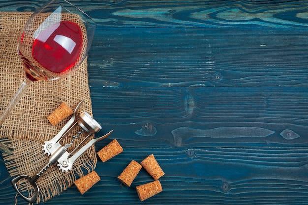 Garrafa de vinho e cortiça e saca-rolhas na mesa de madeira