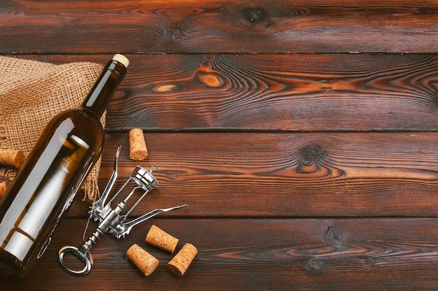 Garrafa de vinho e cortiça e saca-rolhas no fundo da mesa de madeira