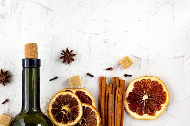 Garrafa de vinho e especiarias em branco. ingredientes para um vinho quente.
