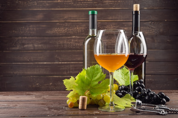 Garrafa de vinho e uva na mesa de madeira