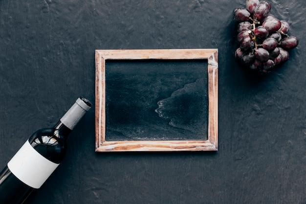 Garrafa de vinho e uva perto do quadro-negro
