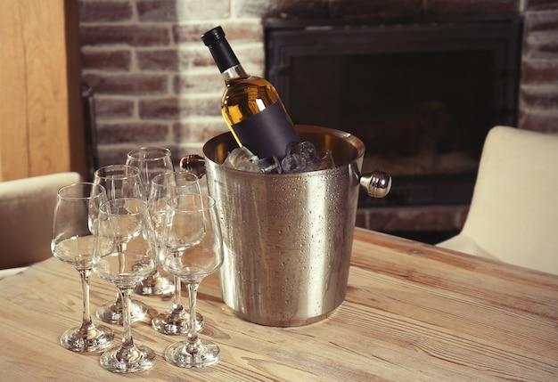 Garrafa de vinho no balde com gelo e copos na mesa