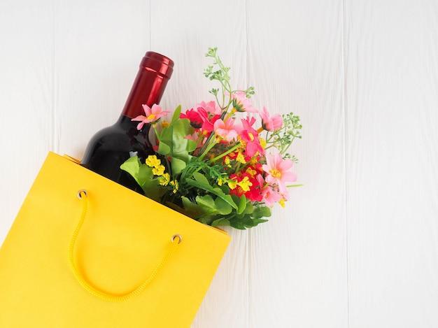 Garrafa de vinho no pacote com flores, plana leigos