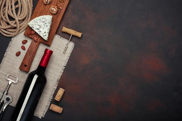 Garrafa de vinho, noz, amêndoas, saca-rolhas e rolhas, vista superior