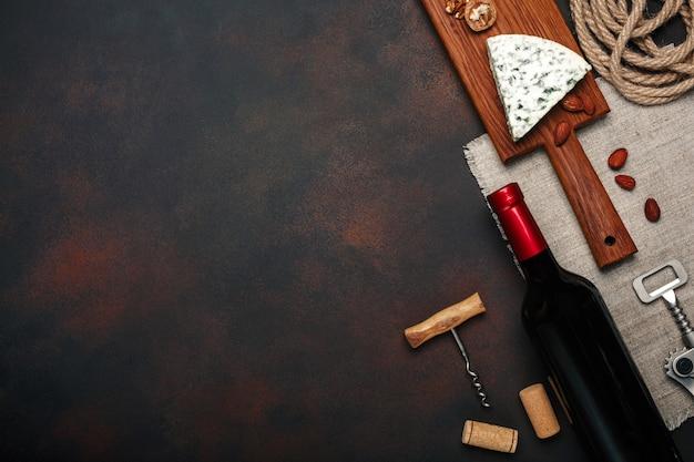 Garrafa de vinho, noz, queijo azul, amêndoas, saca-rolhas e rolhas, na vista superior de fundo enferrujado