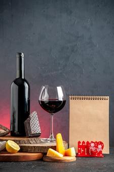 Garrafa de vinho preta de vista frontal com queijo de vidro cortado em pedaços de limão do chocolate amargo em tábuas de madeira na mesa vermelha