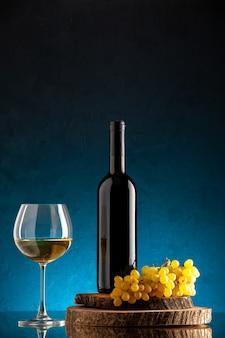 Garrafa de vinho preta de vista frontal, copo de vinho, uvas frescas na placa de madeira na mesa azul