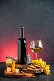 Garrafa de vinho preta de vista frontal vinho tinto em queijo de vidro corte limão, um pedaço de uvas de biscoitos de chocolate amargo em tábuas de madeira na mesa vermelha escura