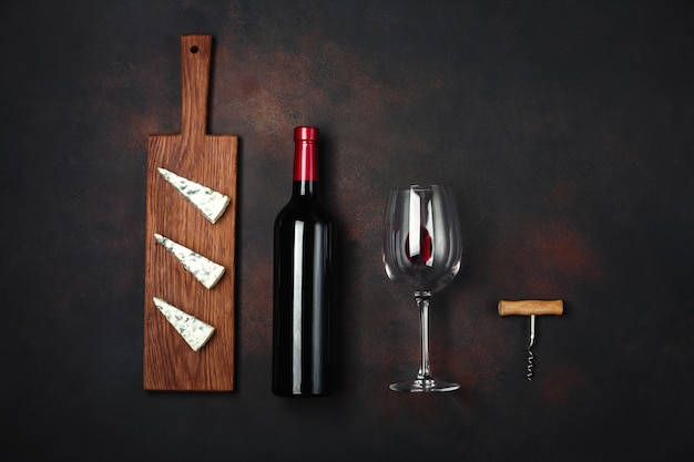 Garrafa de vinho, queijo stinky azul, saca-rolhas e um copo de vinho no fundo enferrujado