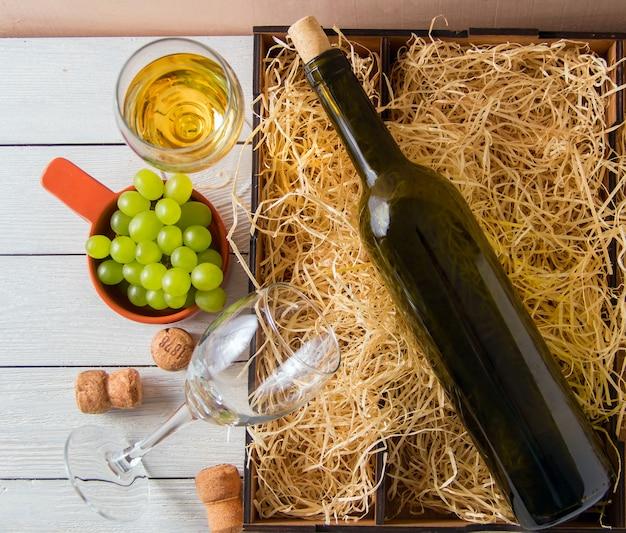 Garrafa de vinho, rolhas, uvas em caixa de madeira. vista do topo.