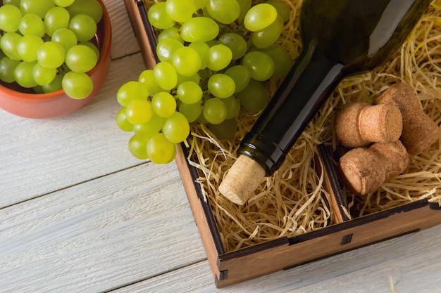 Garrafa de vinho, rolhas, uvas em caixa de madeira