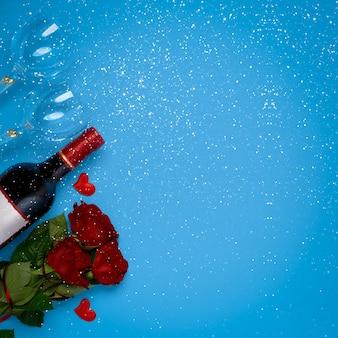 Garrafa de vinho, rosas e taças de vinho com flocos de neve na vista superior de fundo azul com lugar para inserir texto. conceito de dia dos namorados