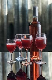 Garrafa de vinho rosé com quatro taças em uma mesa com um reflexo.