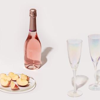 Garrafa de vinho rosé e duas taças de cristal de maçã em um prato transparente na superfície da luz