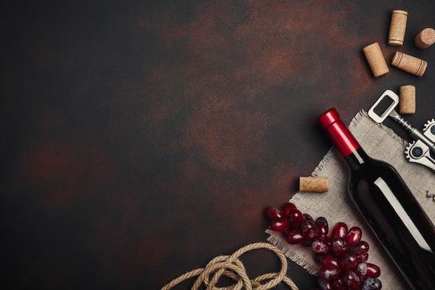 Garrafa de vinho, saca-rolhas e rolhas, na vista superior de fundo enferrujado