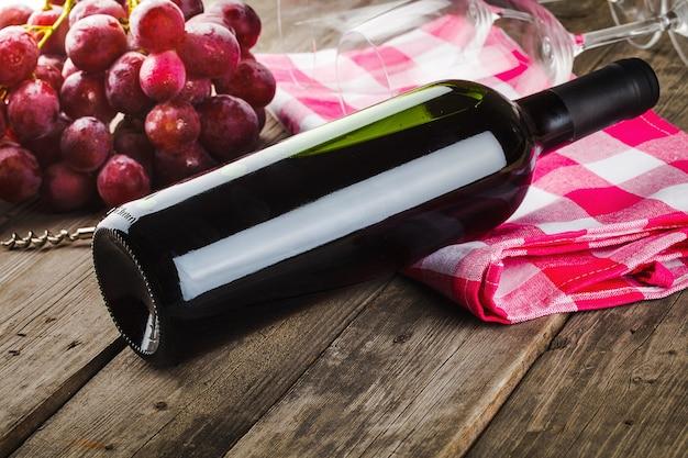 Garrafa de vinho saca-rolhas e uvas na mesa de madeira