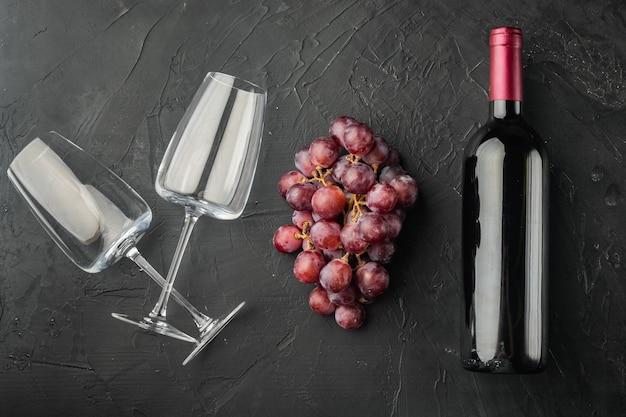 Garrafa de vinho, taça de vinho, conjunto de uvas, mesa de pedra preta, vista de cima plana
