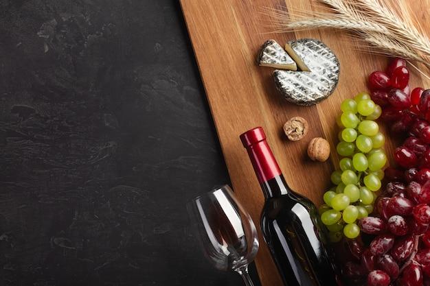 Garrafa de vinho tinto, cacho de uvas, queijo, espigas de trigo e um copo de vinho na placa de madeira