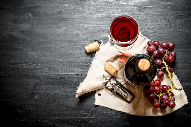 Garrafa de vinho tinto com cacho de uvas em tecido velho na mesa de madeira preta.
