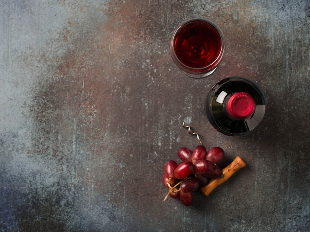 Garrafa de vinho tinto com copos com bebida e uvas em fundo escuro, vista de cima, cópia espaço