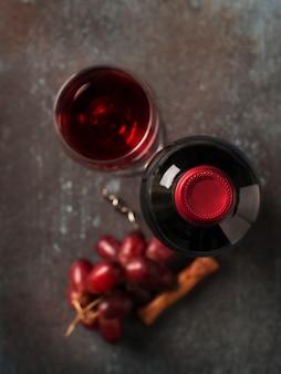 Garrafa de vinho tinto com copos com bebida e uvas em fundo escuro, vista de cima, espaço de cópia, vertical