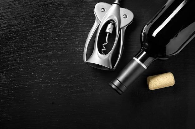 Garrafa de vinho tinto com saca-rolhas na mesa escura