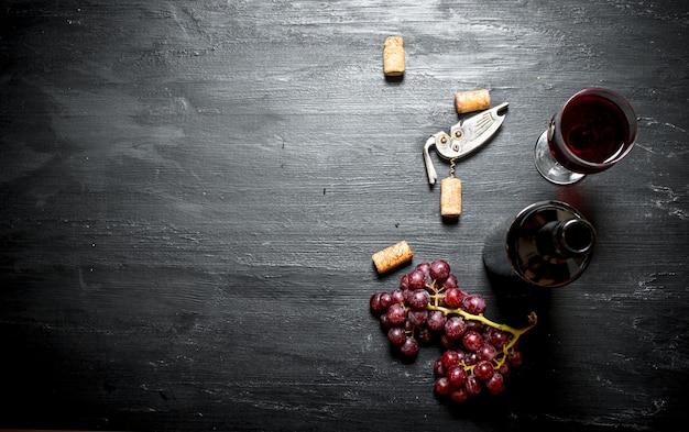 Garrafa de vinho tinto com um saca-rolhas na mesa de madeira preta.