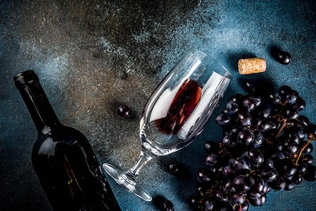 Garrafa de vinho tinto com vidro e uvas