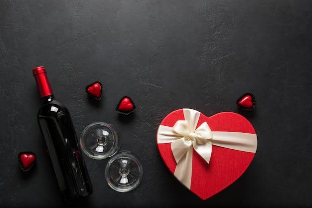 Garrafa de vinho tinto, copo de vinho e presente de coração em fundo preto. cartão de dia dos namorados. vista de cima. espaço para texto.