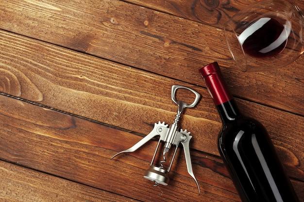 Garrafa de vinho tinto, copo de vinho e saca-rolhas no fundo da mesa de madeira