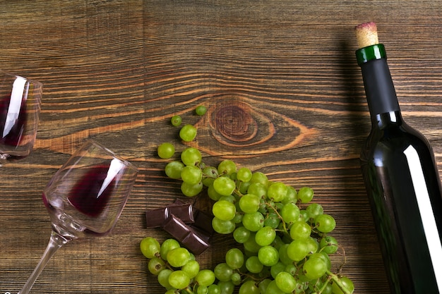 Garrafa de vinho tinto de uva com chocolate e copos sobre mesa de madeira vista com espaço de cópia