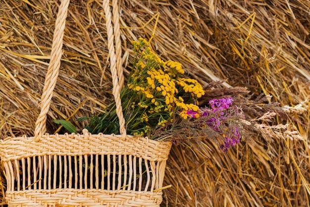 Garrafa de vinho tinto, duas taças e flores silvestres em uma cesta no campo e um feixe