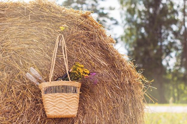 Garrafa de vinho tinto, duas taças e flores silvestres na cesta no campo e o feixe. data romantica.