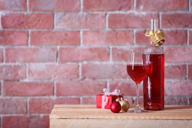 Garrafa de vinho tinto e copo com presentes de natal na parede