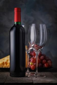 Garrafa de vinho tinto e dois copos vazios em close-up em uma mesa de madeira