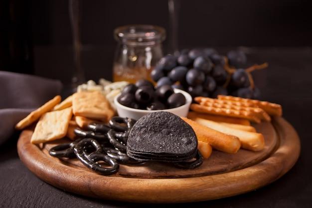 Garrafa de vinho tinto e prato com queijo sortido, frutas e outros petiscos para festa.