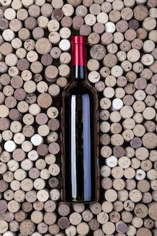 Garrafa de vinho tinto e rolhas na mesa de madeira