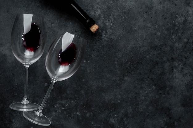 Garrafa de vinho tinto e taças com vinho. vista superior com espaço de cópia.
